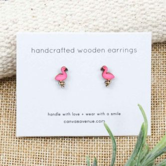 Cute stud style flamingo earrings on an earring card and sitting on a linen background