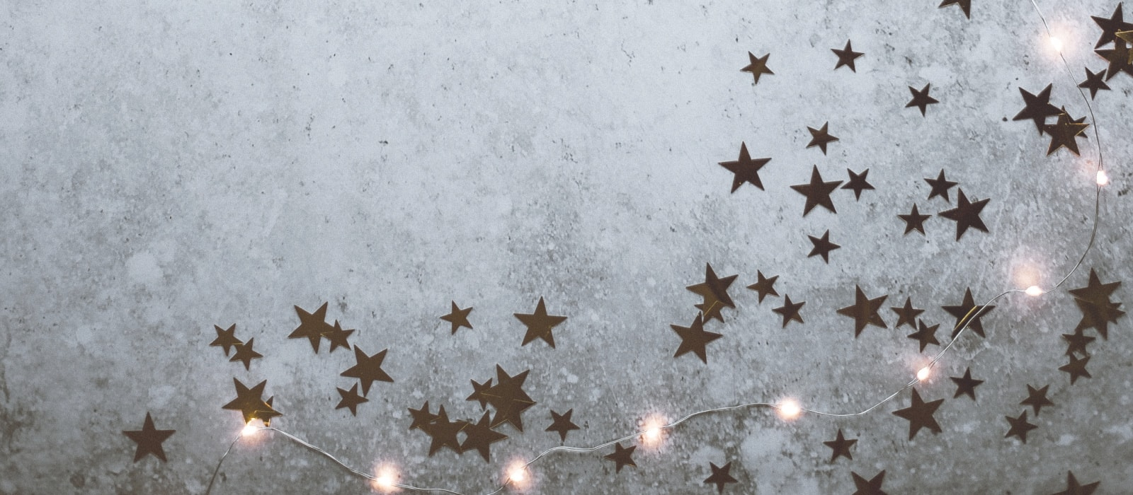 Christmas Etiquette Tips | Horizontal grey background with gold star glitter and a string of white Christmas lights