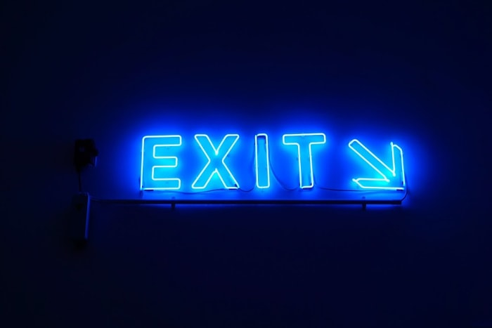 glowing neon blue exit sign with angled arrow