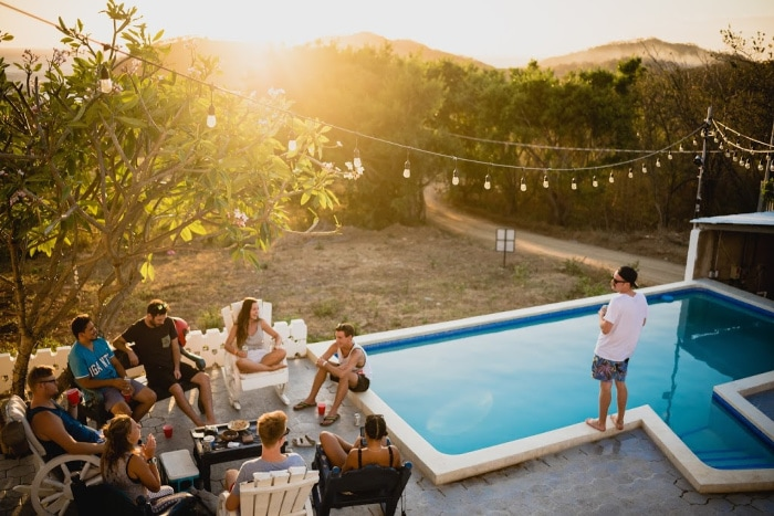 Introvert standing by pool outdoors with group of people in chairs to the right