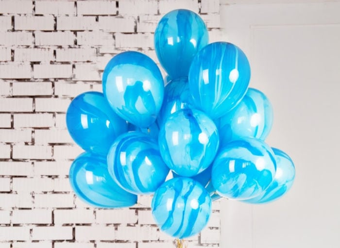 bundle of blue balloons in front of a white brick wall, with gold ribbon