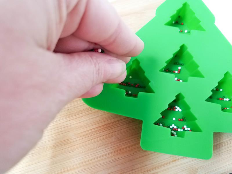 pouring sprinkles into Christmas tree mould