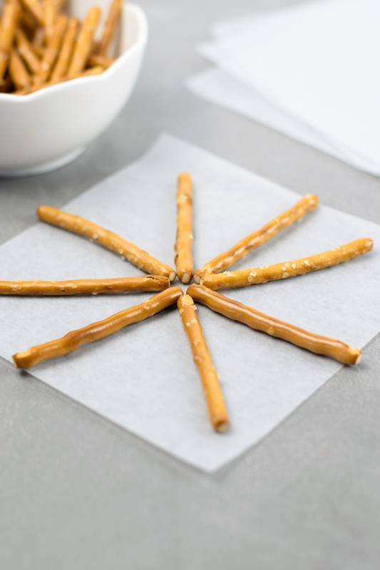 pretzels arranged on parchment paper for making spooky Halloween snack