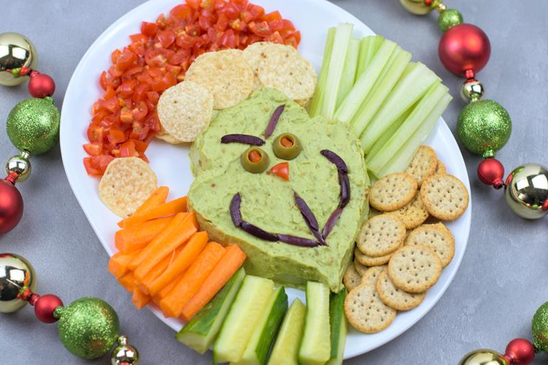 Grinch guacamole platter with dippable treats veggies and chip spread